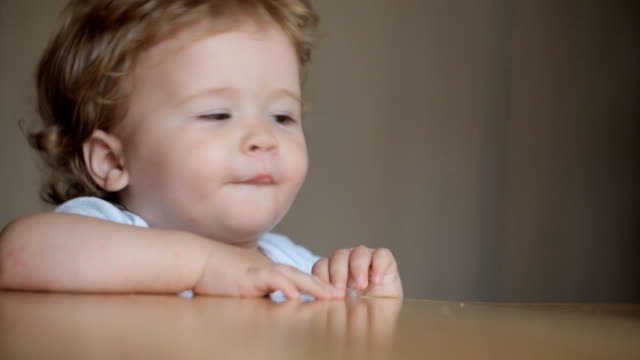 Cute little baby feeding with a spoon at the table, boy eating solid foods video