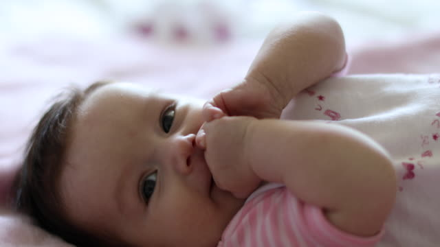 Cute little baby laying on pink blanket in parent's bed video