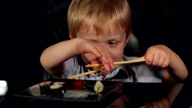 Cute little boy eats sushi wooden chopsticks. video