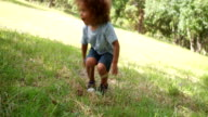 Cute little boy is sitting on the grass in a park video