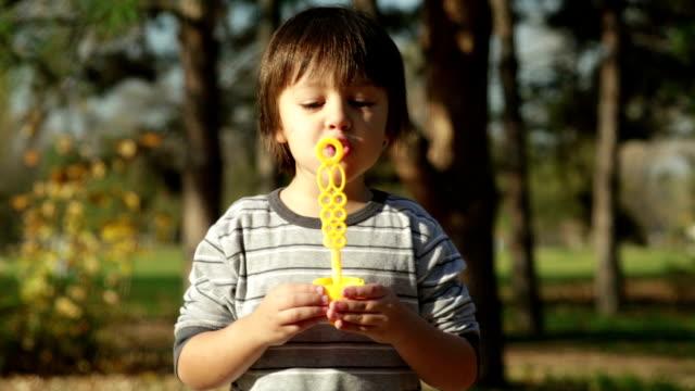 Cute little boy outdoors blowing bubbles video