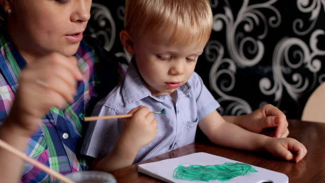 Cute little boy painting with his mother at home. video