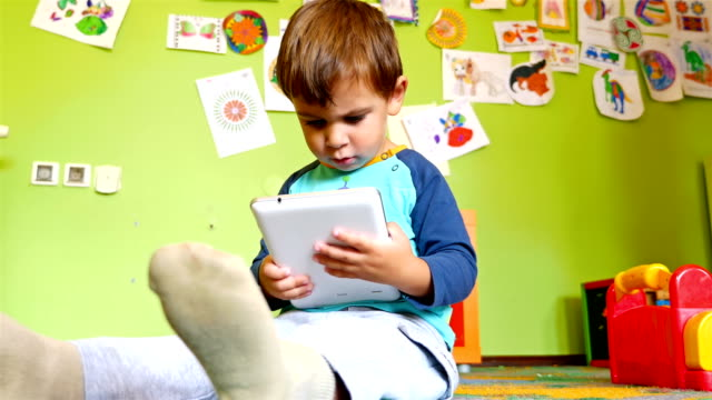 Cute little boy playing game on tablet computer in a colourful room video