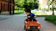 Cute little boy sits in a toy car video