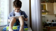 ZOOM: A cute little boy sits on a windowsill and touches a tablet PC video