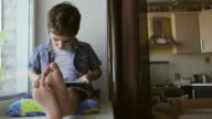 A cute little boy sits on a windowsill at home and touches a tablet PC video