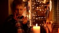 Cute little boy sitting on the windowsill counting days remaining till Christmas video