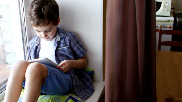 TOP VIEW: A cute little boy uses a tablet PC on a windowsill video