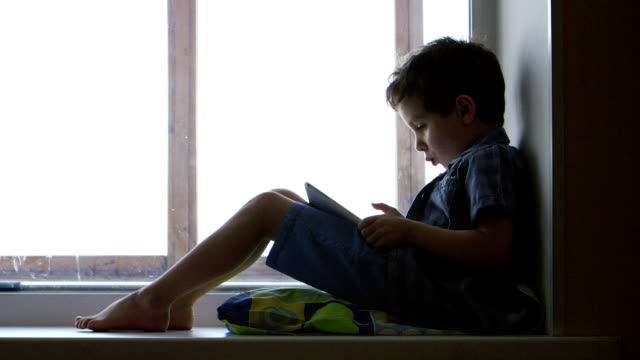 SIDE VIEW: A cute little boy uses a tablet PC on a windowsill video