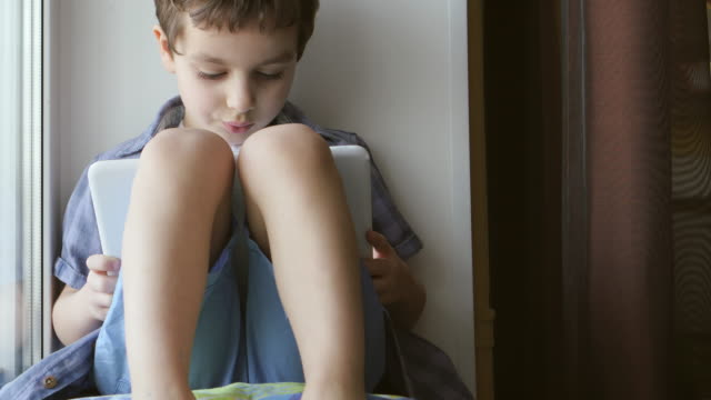 A cute little boy uses a white tablet PC on a windowsill at home video