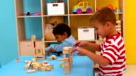 Cute little boys playing with building blocks video