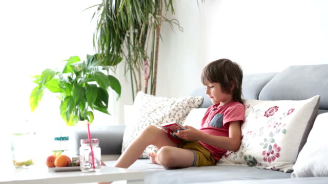 Cute little child, reading a book with pictures at home, sitting on the sofa, smiling and eating fruits video