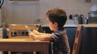 SIDE VIEW: A cute little child uses a tablet PC at a table at home. Casual clothes video