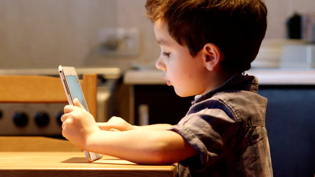 PORTRAIT: A cute little child uses a tablet PC at a table video