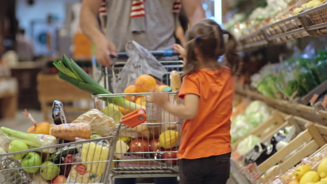 Cute little girl choosing fruits and vegetable with her father video
