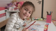 Cute little girl coloring then smiling and looking at camera video