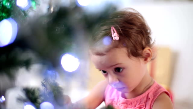 Cute little girl decorates the Christmas tree. video
