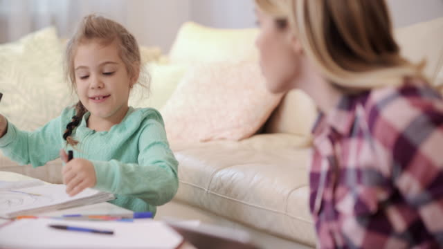 Cute little girl drawing on the paper and talking to her mother. video