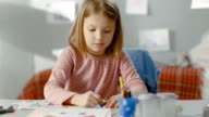 Cute Little Girl Draws with Crayons in Her Light Room. video