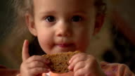 Cute little girl eating a cookie, close up video