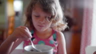 A cute little girl eating cereal at a kitchen counter video