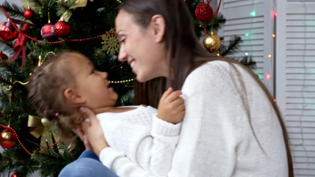 Cute little girl having fun and kissing her mom next to Christmas tree video