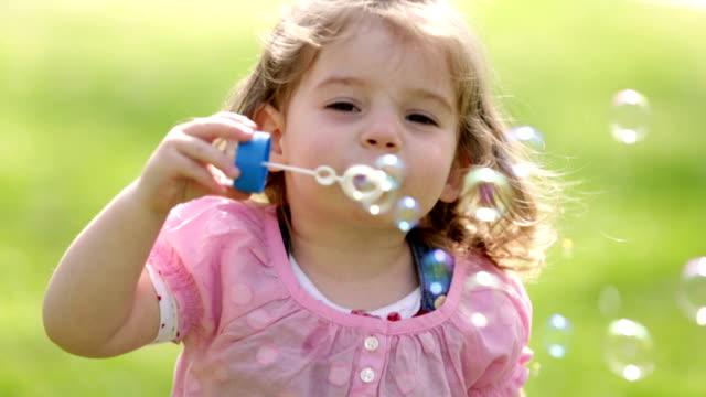 Cute little girl having fun blowing soap bubbles video