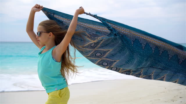 Cute little girl having fun running with pareo on tropical beach video