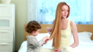 Cute little girl helps her mother combed her long hair, sitting on the bed in the bedroom. video