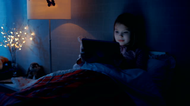 Cute Little Girl in Her Bedroom Lies in Bed With Tablet Computer. video