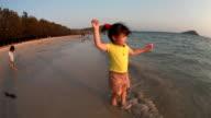 Cute little girl is walking on the beach video