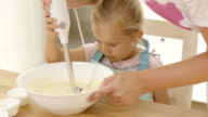 Cute little girl learning to bake from mother video