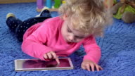 Cute little girl lie on stomach and use tablet computer video