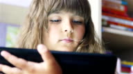 Cute little girl playing with a digital tablet video