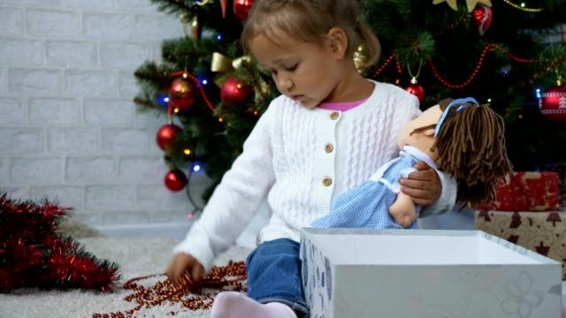 Cute little girl playing with garland near gift box and decorated Christmas tree video