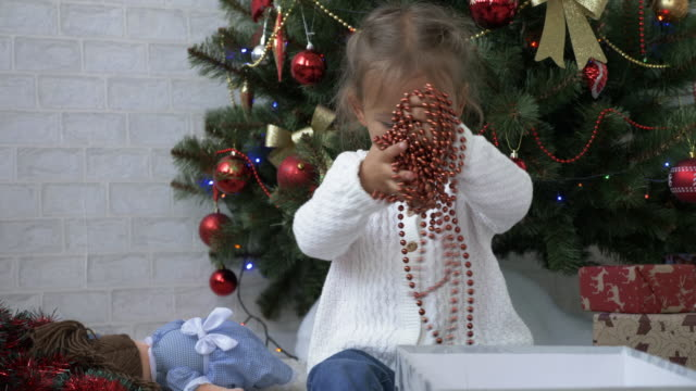 Cute little girl playing with gift box and garland near decorated Christmas tree video