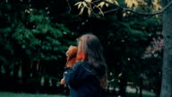 cute little girl playing with her teddy bear hugs and holds it to her yellow leaves fall on them from the tree slow mo video