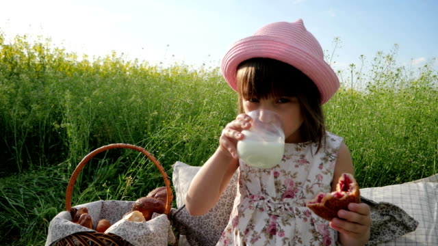 Cute little girl portrait drinks milk, eating bun, Croissant at sunset, child Picnic nature, kid on family picnic, Children at Lunch Time video