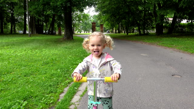 cute little girl riding scooter at park road video