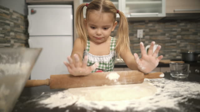Cute little girl rolling raw dough in the kitchen. video