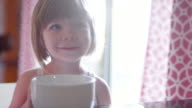 A cute little girl sitting at a kitchen counter with a bowl in front of her video