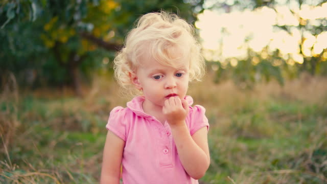 A cute little girl standing in a field and biting her nails video