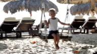Cute little girl swinging on the sandy beach video