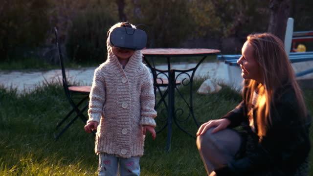 A cute little girl uses a virtual reality helmet video