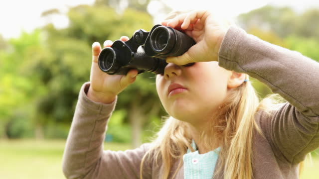 Cute little girl using binoculars in park video