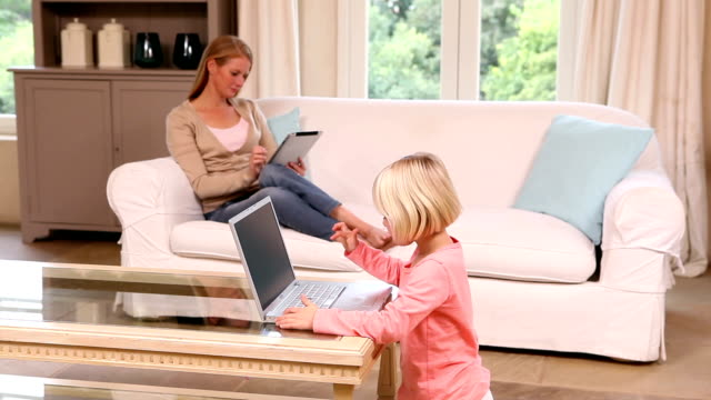 Cute little girl using laptop while mother uses tablet video