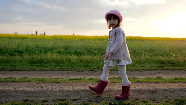 Cute little girl walking in backlight, country road, female child portrait background of field with flowers, healthy childhood video