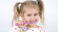 Cute little girl with pigtails diligently brushing his teeth. In the hand of the girl has toothbrush. Cheerful girl looking into the camera. video