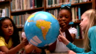 Cute little girls looking at globe in library video