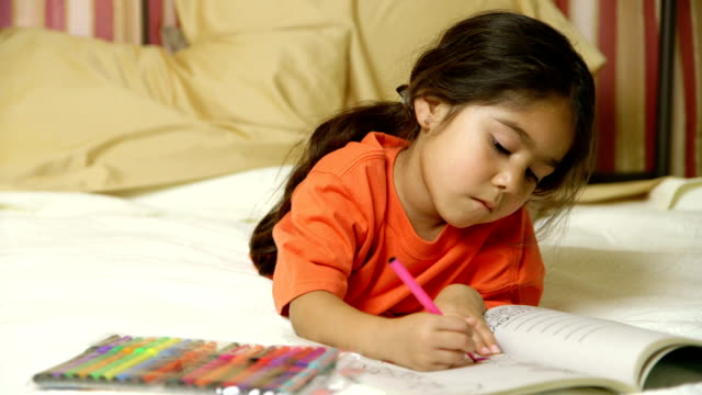 Cute little Hispanic girl on bed coloring in book video